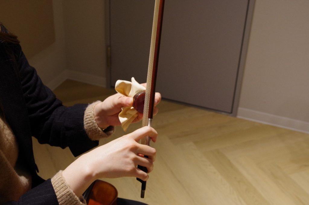 バイオリンの弓に松やにを塗っていきます