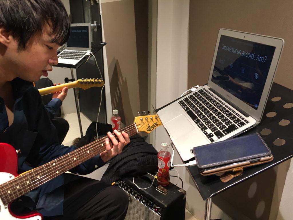 アンプにつないでギターを弾く先生